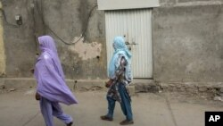 Local women walk past locked house of Christian girl in a suburb of Islamabad, Aug. 20, 2012.