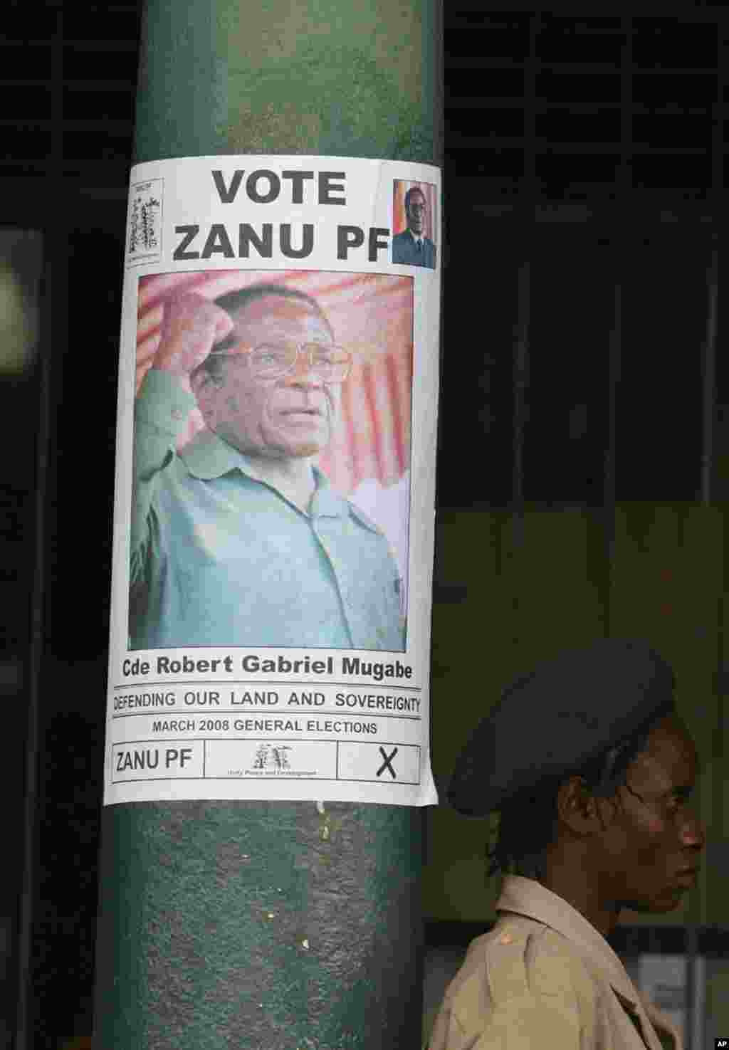 A security guard stands next to a President Robert Mugabe campaign poster in Harare, Zimbabwe, Tuesday, February, 26, 2008.