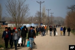 FILE - Migrants walk in Edirne at the Turkish-Greek border, March 9, 2020.