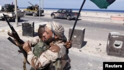 "Anti-Gaddafi fighters embrace as they celebrate the fall of Muammar Gaddafi in Sirte October 20, 2011. Gaddafi was killed by Libyans he once scorned as ""rats"", succumbing to wounds, some seemingly inflicted after his capture by fighters who overran his la"