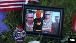 Foto korban terlihat di antara kumpulan benda-benda yang diletakkan di depan Pusat Karir Angkatan Bersenjata/Garda Nasional di Chattanooga, Tennessee, untuk mengenang para korban yang tewas dalam penembakan hari Kamis.