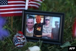 A photograph of the victims is seen among the memorial setup in front of the Armed Forces Career Center/National Guard Recruitment Office in Chattanooga, Tennessee, July 18, 2015.