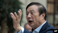 FILE - Ren Zhengfei, founder and CEO of Huawei, gestures during a meeting with reporters in Shenzhen city, south China's Guangdong province, Jan. 15, 2019.