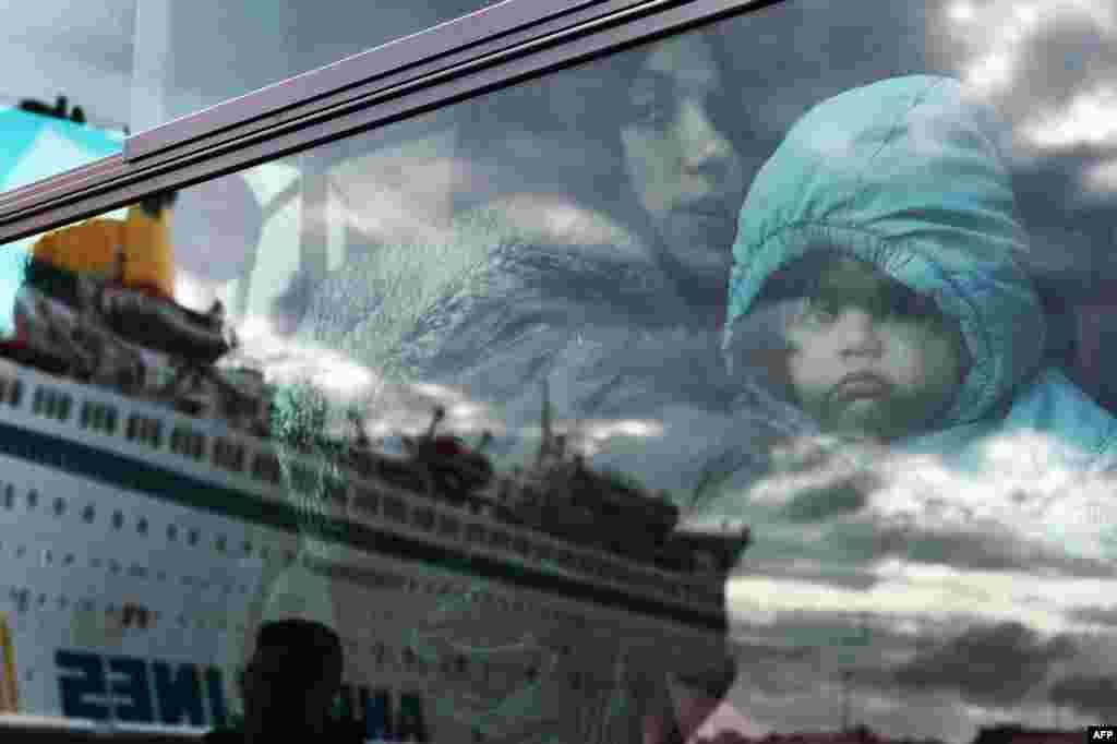 Một người phụ nữ và một em bé trên một chiếc xe buýt đưa rước người tị nạn tại cảng Piraeus ở thủ đô Athens, Hy Lạp.