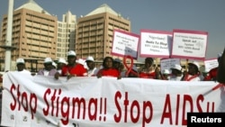 People holding banners march to campaign for increased aids awareness in the streets of Nigeria's capital Abuja, December 1, 2006, on World Aids Day.