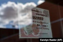 Sebuah peringatan untuk mengenakan masker dipasang di pintu Pusat Kesehatan Kayenta di reservasi Navajo di Kayenta, Arizona, 18 April 2020. (Foto: dok).
