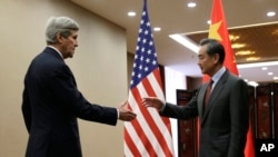 U.S. Secretary of State John Kerry, left, prepares to shake hands with Chinese Foreign Minister Wang Yi at the Ministry of Foreign Affairs in Beijing, Jan. 27, 2016.