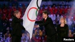 在索契冬奧會閉幕式上,國際奧委會主席巴赫把奧林匹克旗幟交給南韓平昌市市長李熙來。 (2014年2月23日)