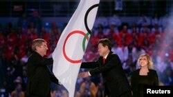 Chủ tịch Ủy ban Olympic quốc tế (IOC) Thomas Bach trao cờ Olympic cho Thị trưởng thành phố PyeongChang Lee Sok-ra trong lễ bế mạc Thế vận hội Sochi 2014, ngày 23/2/2014.