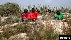 Des migrants sont assis devant le centre d'immigration sur l'île de Lampedusa, dans le sud de l'Italie, le 19 février 2015.