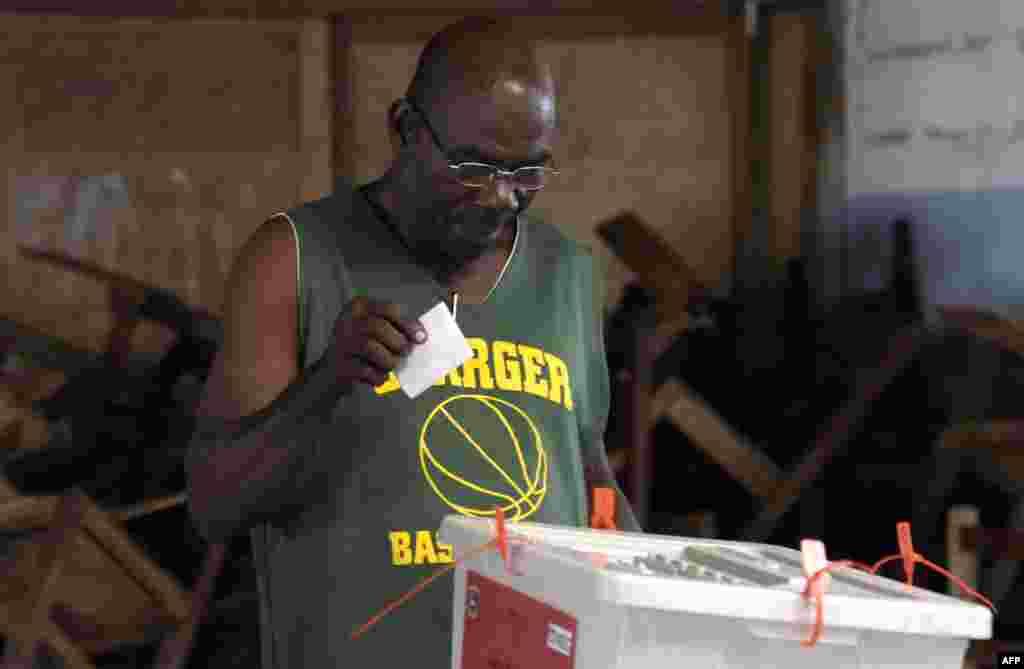 Un électeur libérien met son bulletin de vote dans une boîte à un bureau de vote, à Monrovia, le 26 décembre 2017.