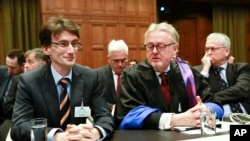 FILE - Members of the Serbian delegation, First Counsellor Sasa Obradovic, left, William Schabas, center and Andreas Zimmermann, right, await the start of public hearings at the International Court of Justice (ICJ) in The Hague, Netherlands, March 3, 201