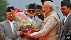 ນາຍົກລັດຖະມົນຕີອິນເດຍ ທ່ານ Narendra Modi ຜູ້ທີສອງຈາກຂວາ ໄດ້ຮັບຊໍ້ດອກໄມ້ ຈາກຄູ່ຕຳແໜ່ງ ເນປາລ ທ່ານ Sushil Koirala ຫຼັງຈາກເດີນທາງໄປຮອດ ເດີ່ນບິນ ສາກົນ Tribhuwan ໃນນະຄອນຫລວງກັດມັນດູ ປະເທດເນປາລ ເມື່ອວັນທີ 3 ສິງຫາ 2014.