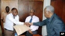 Mutamwega Mugahywa (kushoto) mgombea kiti cha rais kwa niaba ya chama cha TLP akichukua fomu za kushiriki katika uchaguzi wa rais.