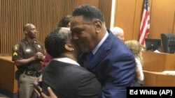 Richard Phillips, right, hugs Det. Patricia Little in a courtroom on Wednesday, March 28, 2018, in Detroit, Michigan. Phillips, a Michigan man whose murder conviction was thrown out after he spent 45 years in prison will not face a second trial. (AP Photo/Ed White)