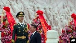 中国主席习近平在北京的人民英雄纪念碑前向烈士致敬后走过纪念碑(2014年9月30日)