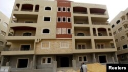 FILE - A man looks at a newly constructed residential building in El Maraj city at New Maadi, south of Cairo.