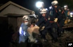 In this image made from video and provided by Kumamoto Prefectural Police, eight-month-old baby Miku Nishimura is carried away after being rescued from her home, which collapsed in a magnitude-6.5 earthquake in Mashiki town, Kumamoto prefecture, southern Japan, early Friday, April 15, 2016.