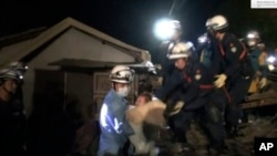 In this image made from video and provided by Kumamoto Prefectural Police, eight-month-old baby Miku Nishimura is carried away after being rescued from her home, which collapsed in a magnitude-6.5 earthquake in Mashiki town, Kumamoto prefecture, southern