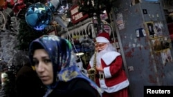 A woman walks past by a store selling New Year and Christmas ornaments in Istanbul, Turkey, Dec. 22, 2015. Turkey on Wednesday detained two suspected Islamic State members believed to be planning suicide attacks on New Year's celebrations in the country's capital.