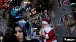 Seorang perempuang tengah berjalan melewati penjual ornamen Natal dan Tahun Baru di Istanbul, Turki (22/12).