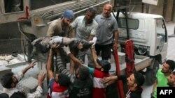 Lực lượng tình nguyện viên dân phòng Syria, còn được gọi là mũ bảo hiểm trắng, truyền tay nhau cơ thể của một cậu bé được lôi lên từ đống đổ nát sau một cuộc không kích của lực lượng chính phủ tại khu phố al-Shaer, khu vực do phiến quân kiểm soát, thuộc thành phố Aleppo, ngày 27 tháng 09 năm 2016.