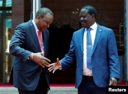 Kenya's President Uhuru Kenyatta, left, shakes hands with opposition leader Raila Odinga of the National Super Alliance coalition following a joint news conference at the Harambee house office in Nairobi, Kenya, March 9, 2018.