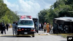 FILE - The lifeless body of a passenger lies next to an overturned bus, as ambulances, firefighters and police stand by in Mahahual, Quintana Roo state, Mexico, Dec. 19, 2017.