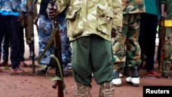 FILE - A former child soldier poses with his gun. According to UNICEF, an armed group fighting Boko Haram in Nigeria has released hundreds of child soldiers that had been recruited into its ranks.