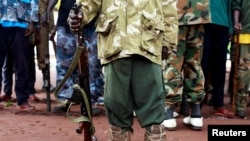 FILE - A former child soldier poses with his gun in this undated photo.