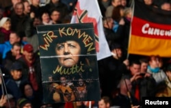 "FILE - Supporters of the anti-Islam movement PEDIGA hold a poster depicting German Chancellor Angela Merkel with text reading ""We are coming, mommy!"" during a demonstration in Dresden, Germany, Feb. 6, 2016."