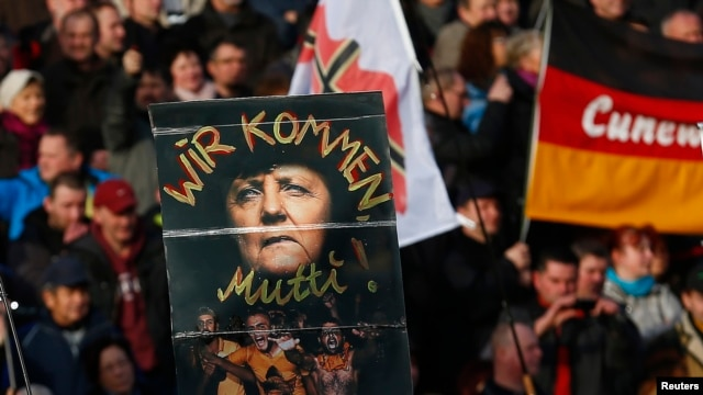 """Supporters of the anti-Islam movement Pegida hold a poster depicting German Chancellor Angela Merkel with text reading """"We are coming, mommy!"""" during a demonstration in Dresden, Germany, Feb. 6, 2016."""