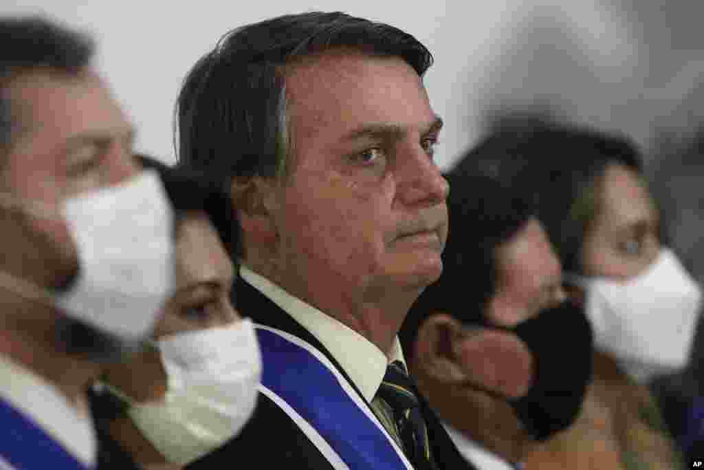 Brazil's President Jair Bolsonaro listens to his nation's anthem during a ceremony marking Diplomat Day at Itamaraty Palace in Brasilia, Brazil, Thursday, Oct. 22, 2020, amid the COVID-19 pandemic. (AP Photo/Eraldo Peres)