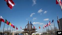 (资料照片)北大西洋公约组织布鲁塞尔总部外,北约的象征雕塑和成员国的旗帜。