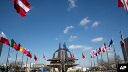 Simbol NATO dan bendera negara-negara yang bergabung dalam organisasi NATO terlihat berkibar di luar Markas Besar NATO di Brussels. (AP Photo/Virginia Mayo)