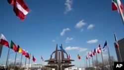 Archivo - Símbolo de la OTAN y banderas de las naciones de la OTAN fuera de la sede en Bruselas.