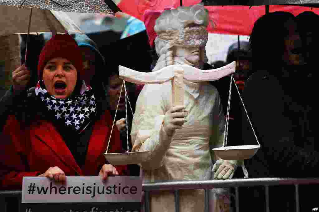 A woman dressed as Lady Justice joins over 100 protesters, many of them women, at a rally in heavy rain outside of the offices of Democratic Senators Chuck Schumer and Kirsten Gillibrand to demand that they hold up the nomination process of President Donald Trump's cabinet choices, in New York City.