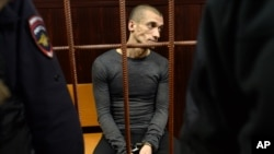 Russian performance artist Pyotr Pavlensky, seen in this Nov. 10, 2015 photo, sits in a court room before a hearing on his case in Moscow, Russia. He's convicted Thursday of vandalism for a pro-Ukraine protest and sentenced to 16 months in prison.