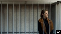 Nhà hoạt động của Tổ chức Greenpeace Paula Alminhana Maciel đứng trong cũi sắt tại Tòa án quận Murmansk của Nga, ngày Chủ Nhật 29/9/2013.