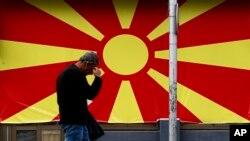 ARHIVA - Stanovnik Skoplja prolazi pored zastave Severne Makedonije (Foto: AP/Boris Grdanoski)