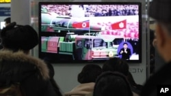 Warga Seoul, Korea Selatan menyaksikan siaran berita yang menampilkan cuplikan film tentang roket Korea Utara yang ikut dipamerkan dalam arak-arakan di sebuah parade militer (24/1). Korut mengancam akan menindak keras Korea Selatan jika Seoul terlibat langsung dalam resolusi PBB yang memperketat sanksi terhadap Pyongyang.