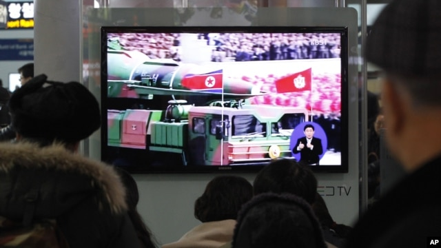 People watch a TV news showing file footage of a North Korean rocket carried during a military parade, at Seoul Railway Station in Seoul, South Korea, January 24, 2013.