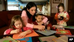 Au pair Wendy Aguirre helps the Lyon children Ella, right; C.J., left; and Jackson with art projects Thursday, Dec. 7, 2006, in Overland Park, Kan. Aguirre, from Panama, is teaching the three 3-year-olds Spanish as part as her duties as the family's au pa