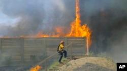 A brush fire burns at a shooting range on the beach at Navel Base Ventura County May 3, 2013
