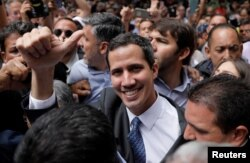 Pemimpin oposisi Venezuela, Juan Guaido dikelilingi para pendukungnya sebelum mengadakan konferensi pers di Caracas, Jumat (25/1).