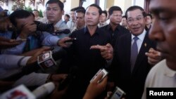 FILE-Cambodia's Prime Minister Hun Sen (2nd R), speaks to media after a meeting at the National Assembly in central Phnom Penh August 8, 2014.