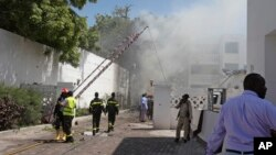 Smoke and steam from fires extinguished with water, clouds the scene of a twin bombing attack on a hotel in the capital Mogadishu, Somalia, Feb. 20, 2015.