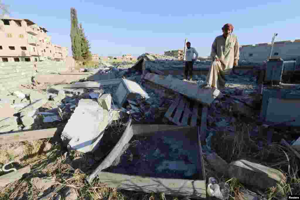 Abu Ismail, the owner of a plastics factory that was targeted on Sunday by what activists said were U.S.-led air strikes, examines the damage at his destroyed factory in the Islamic State's stronghold of Raqqa, Sept. 29, 2014.