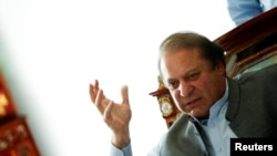 Nawaz Sharif, the leader of Pakistan Muslim League - Nawaz (PML-N), gestures as he speaks to foreign reporters at his residence in Lahore May 13, 2013.