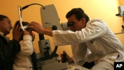 FILE - A doctor performs laser microsurgery on a 2-year-old with congenital cataracts at the Ophthalmology Institute in La Paz, Bolivia, April 26, 2006. Researchers now have discovered a technique that removes the cataracts, and stimulates a child's stem cells to regrow a functioning lens.